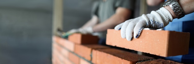 Dos trabajadores haciendo pared de ladrillo rojo en primer plano del sitio de construcción