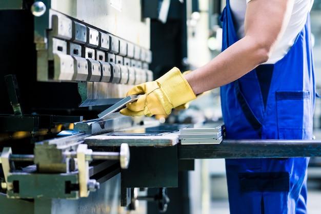 Dos trabajadores industriales inspeccionando la pieza de trabajo de pie en el piso de la fábrica con orejeras y gafas