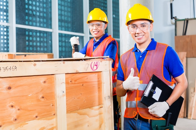 Dos trabajadores industriales o de la construcción indonesios asiáticos que controlan con una lista de verificación una entrega en un sitio de construcción de una torre y abren una caja de madera o un contenedor de carga con una palanca