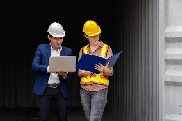 Dos trabajadores ingeniero sostienen una computadora portátil, documento para verificar la calidad de la caja de contenedores del buque de carga para exportación e importación, fondo de contenedor azul