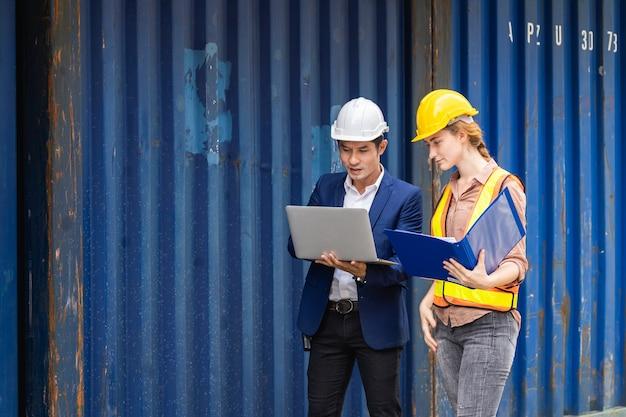 Dos trabajadores ingeniero sostienen una computadora portátil, documento para verificar la calidad de la caja de contenedores del buque de carga