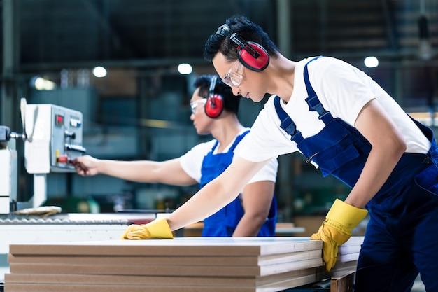Dos trabajadores de la madera en tablas de cortar de carpintería poniéndolos en sierra