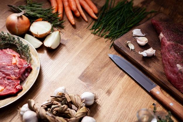 Dos trozos de carne roja junto a verduras frescas en la mesa de madera rústica. cocinando la cena. preparación de comida.