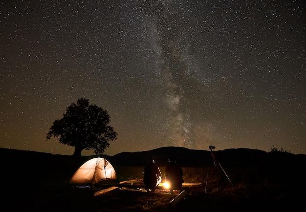 Dos turistas en la quema de fogata frente a la tienda, cámara de fotos en trípode bajo el oscuro cielo estrellado.