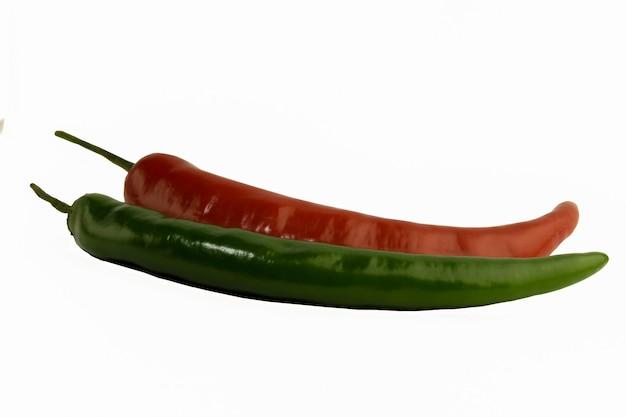 Dos vainas frescas de pimiento rojo y verde de cerca sobre un fondo blanco con colas de caballo verde