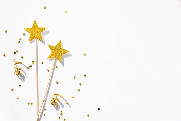 Dos varitas mágicas de fiesta doradas, lentejuelas y cintas sobre un fondo blanco.