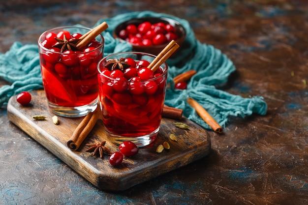 Dos vasos con una bebida caliente de arándanos y manzanas con especias, vino caliente, ponche o grog.