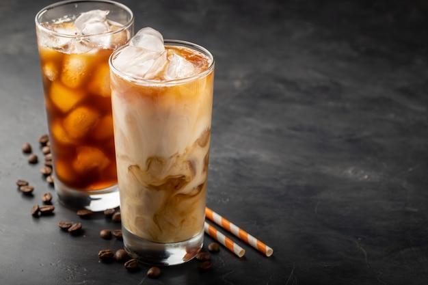Dos vasos de café frío sobre un fondo oscuro.