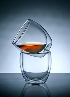 Dos vasos para café o té, uno encima del otro con té en el vaso superior con reflejo