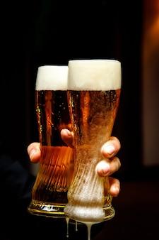 Dos vasos de cerveza con abundante espuma en las manos.