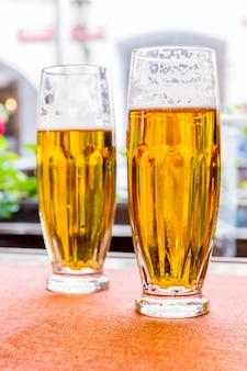 Dos vasos de cerveza fresca sobre la mesa en el pub. mostrador de bebidas en discoteca o restaurante.