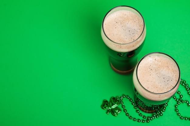 Dos vasos de cerveza negra oscura y decoración tradicional en forma de trébol, composición festiva del día de san patricio