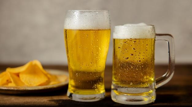 Dos vasos de cerveza y un plato de papas fritas en la mesa. pareja o dos amigos bebiendo cerveza concepto