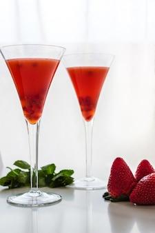 Dos vasos de cóctel de fresa, granada y menta.
