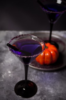 Dos vasos con cóctel morado, calabaza para la fiesta de halloween oscura