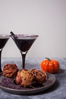 Dos vasos con cóctel negro, rosas secas, calabaza para la fiesta de halloween en el fondo oscuro