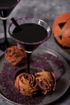 Dos vasos con cóctel negro, rosas secas, jack-o'-lantern para la fiesta de halloween en la oscuridad