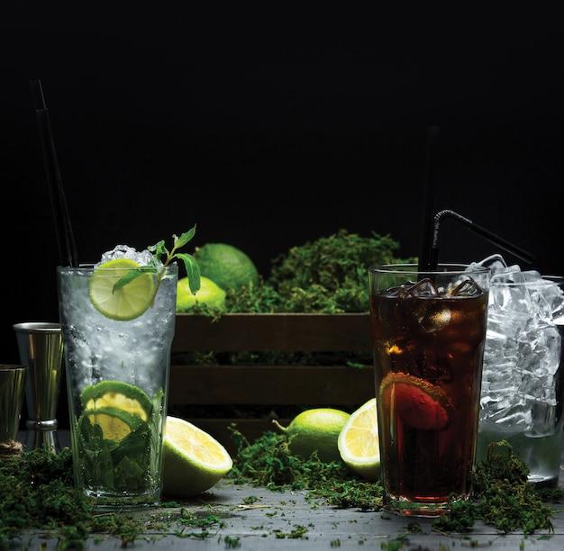 Dos vasos de cócteles fríos de verano con jarabes de frutas y cubitos de hielo.