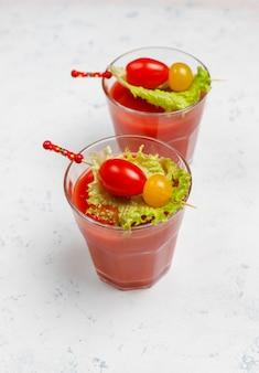 Dos vasos de jugo de tomate fresco y tomates en superficie de hormigón gris