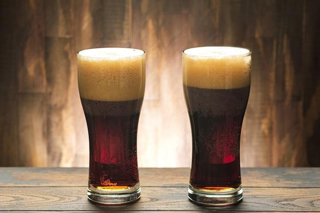 Dos vasos llenos de cerveza oscura y espuma.