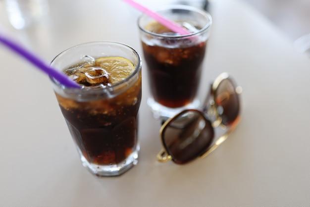 Dos vasos de paja y gafas de sol llenos de pie sobre la mesa blanca