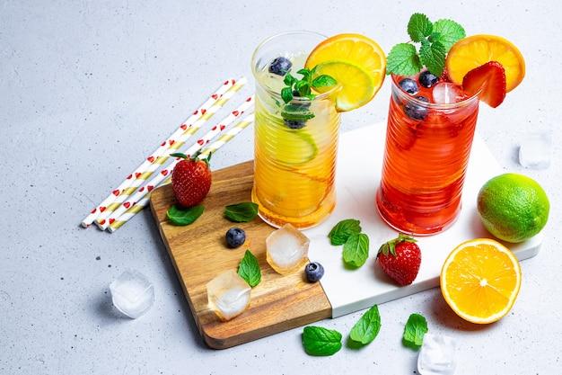 Dos vasos de refrescante limonada de verano con cóctel de hielo con fresa y limón y cóctel