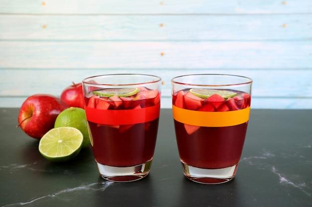 Dos vasos de sangría sobre la mesa con manzanas y limas