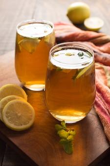 Dos vasos de té de limón y jengibre en mesa de madera