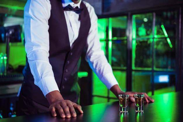 Dos vasos de tequila en barra de bar y barman inclinado