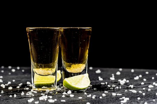 Dos vasos de tequila con limón y sal.