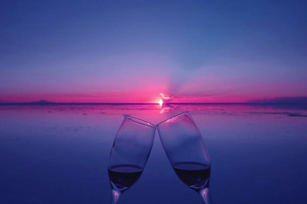 Dos vasos tintinean para celebrar al atardecer sobre inundaciones de salinas, uyuni, bolivia