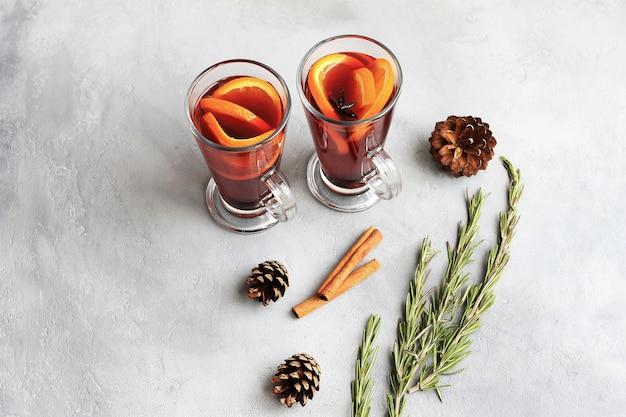 Dos vasos de vino caliente caliente rojo o gluhwein con naranja, palitos de canela