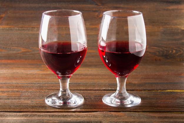 Dos vasos de vino tinto en una mesa de madera marrón. bebidas alcohólicas.