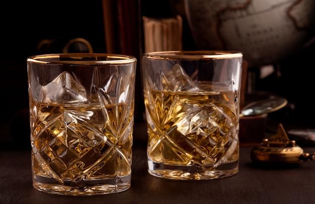 Dos vasos de whisky en la biblioteca.