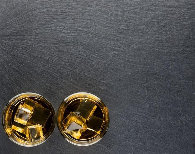 Dos vasos de whisky en el fondo.
