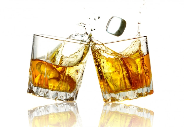 Dos vasos de whisky tintinean juntos, aislados