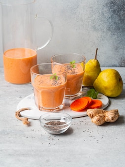 Dos vasos de zanahoria fresca fresca, pera, batido de jengibre con semillas de chía sobre fondo gris