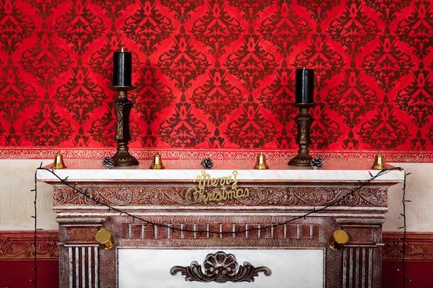 Dos velas en una chimenea sala vintage de navidad sobre un fondo rojo foto de estudio interior de navidad vintage sensasional