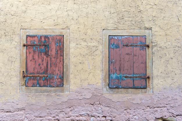 Dos ventanas leñosas en el clásico muro antiguo amarillo plae en europa