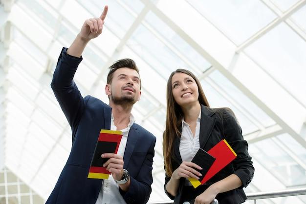 Dos viajeros que comprueban la información de embarque en el aeropuerto.