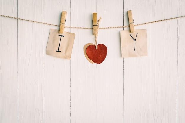 Dos viejo papel en blanco y corazón rojo colgando. sobre fondo blanco de madera con estilo vintage.