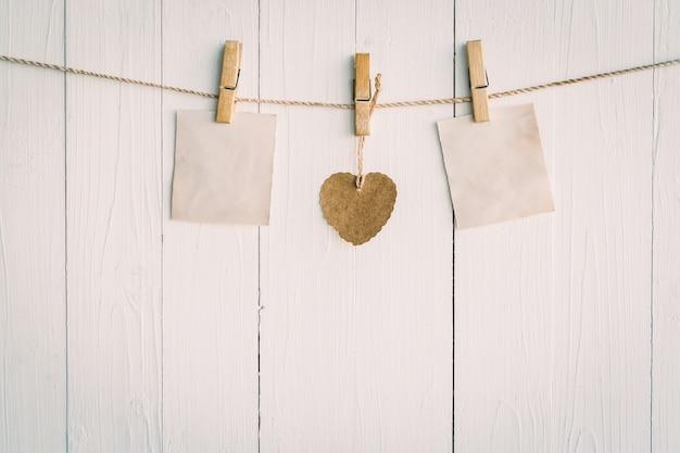 Dos viejos papel en blanco y corazón marrón colgando. sobre fondo blanco de madera con estilo vintage.