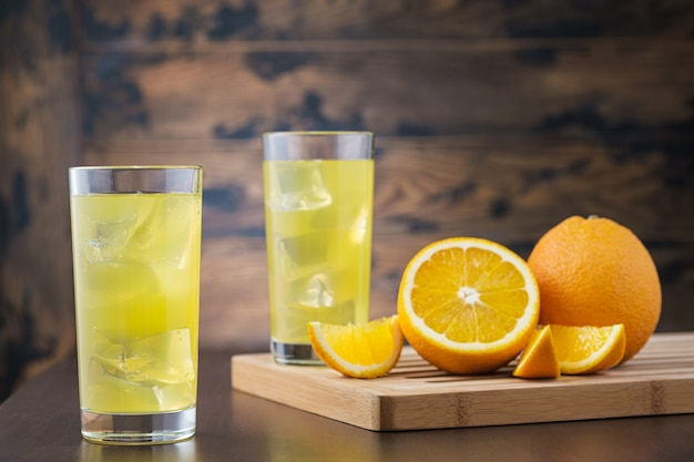 Dos zumo de naranja lleno en vaso con cubitos de hielo en la pared de madera