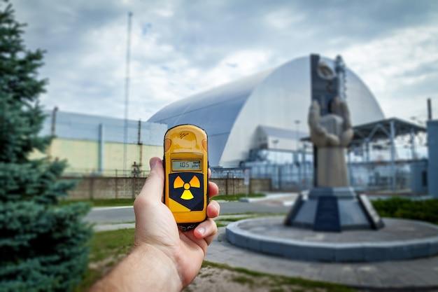 Un dosímetro en manos con un nivel de radiactividad cerca del monumento a los liquidadores de chernobyl cerca del cuarto reactor. historia del desastre de chernobyl. lugar perdido en ucrania, urss