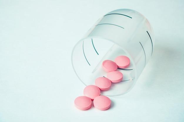 Dosis diaria de medicamento para mantener la salud de las píldoras rosadas en un recipiente de plástico