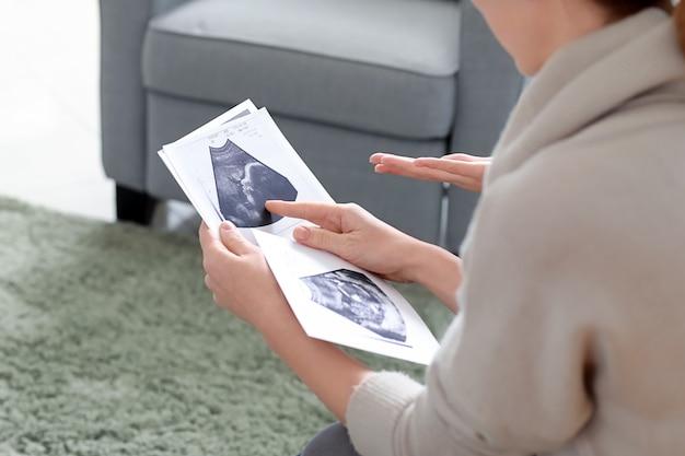 Doula y mujer embarazada con ecografías en casa