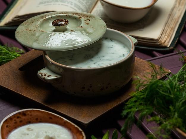 Dovga, sopa de crema de yogur tradicional en una sartén verde