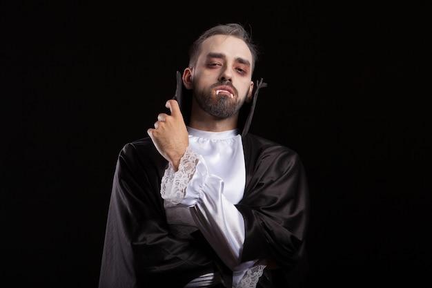 Drácula joven y atractivo manteniendo los brazos cruzados con los dientes hacia fuera para halloween. retrato de hombre disfrazado de drácula. drácula con cara de maldad.