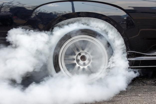 Drag racing car quema goma de sus neumáticos en preparación para la carrera