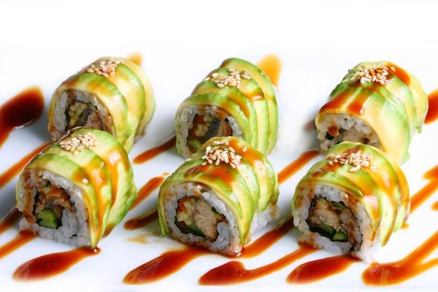Dragon rolls sushi sobre fondo blanco.